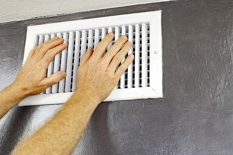 ac blowing hot air, two hands in front of an ac vent