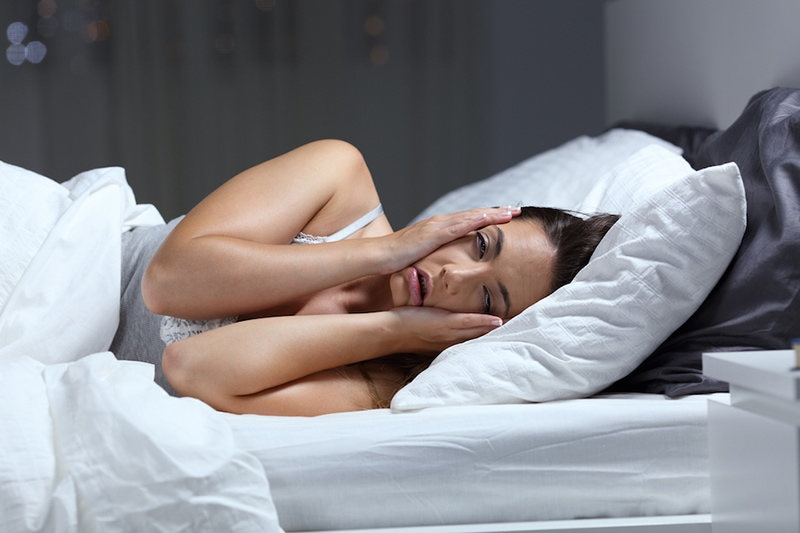 Desperate girl suffering insomnia trying to sleep,3 Health Benefits for Using Your AC While Sleeping