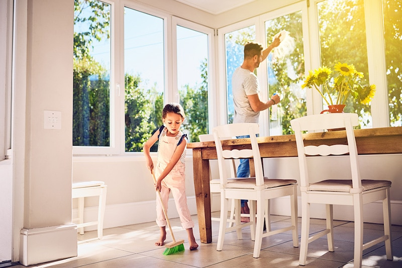 A girl sweeping the floor while her father cleans the windows   How Environmental Issues Can Affect Your AC   Mt. Sterling, KY